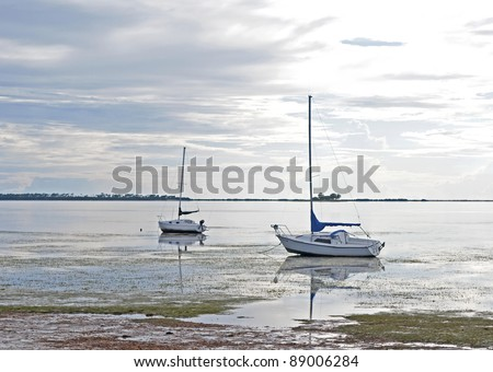 Two sailboats stranded in shallow water on an overcast day. Crystal Beach, Florida.