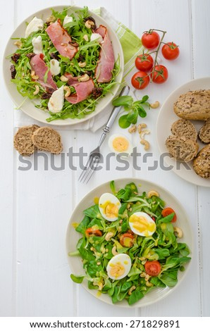 Two salad - Lamb's lettuce salad with eggs and Arugula salad with smoked rump, mozzarella and sundried tomatoes - stock photo