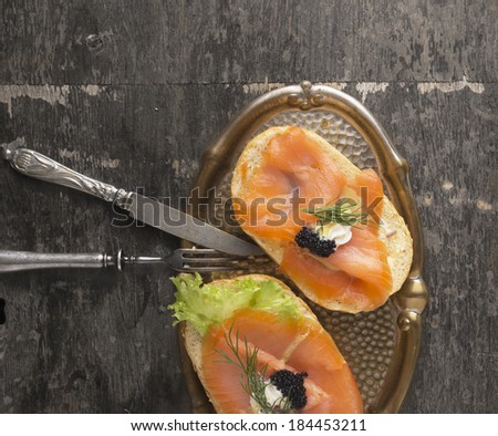 two sandwich with salmon and black caviar , in vintage tray with fork and knife on old wooden table  - stock photo