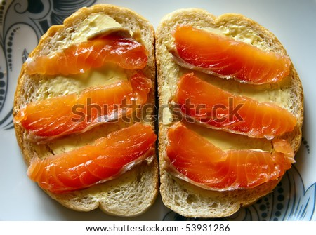 two sandwiches with butter and red smoked salmon on a plate