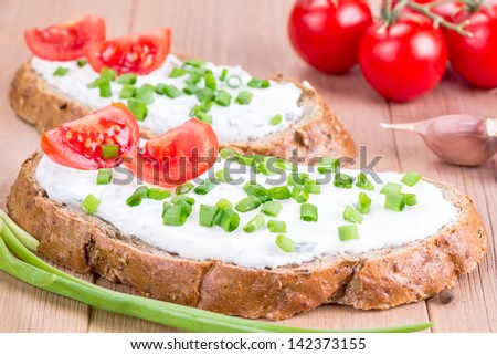 Two sandwiches with cream cheese and tomatoes - stock photo
