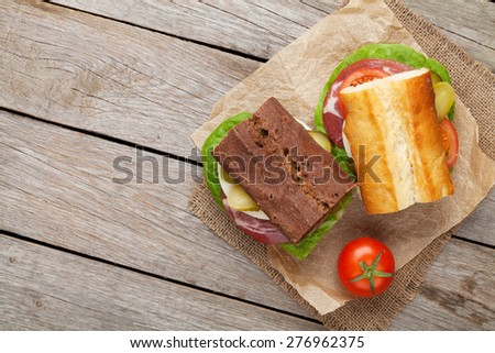 Two sandwiches with salad, ham, cheese and tomatoes on wooden table with copy space - stock photo