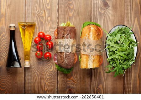 Two sandwiches with salad, ham, cheese and tomatoes, salad and spices on wooden table. Top view with copy space - stock photo