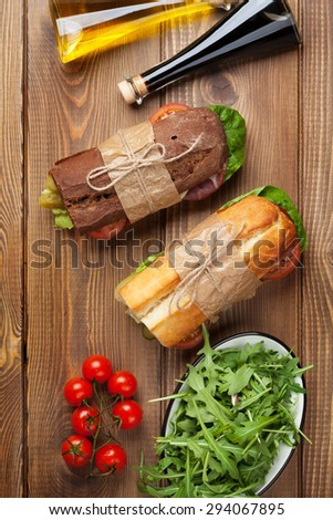 Two sandwiches with salad, ham, cheese and tomatoes, salad and spices on wooden table. Top view - stock photo