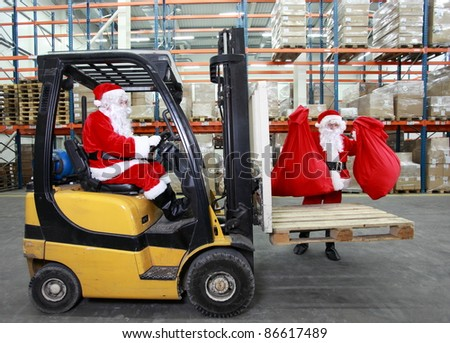 Two santa clauses as a workers in modern storehouse full of goods. One on forklift, another is lifting sacks full of presents. - stock photo