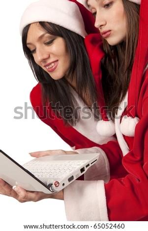 Two santa girls looking at laptop screen - stock photo