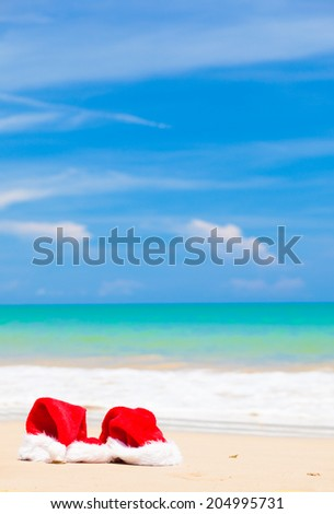 two santa hats lying on tropical sand beach. party. christmas. new year - stock photo