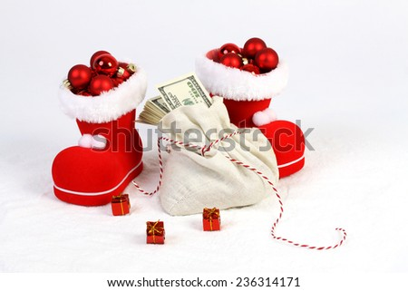 Two Santa shoes with red mat christmas balls and Santa bag with stack of money american hundred dollar bills and three gifts with gold bow on snow - stock photo