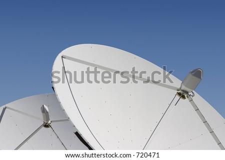 Two satellite dishes point skyward. - stock photo