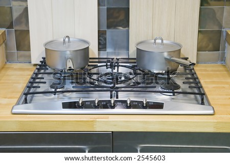 Two saucepans with lids on a gas hob - stock photo