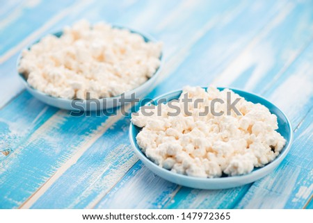 Two saucers with fresh cottage cheese on wooden background, studio shot - stock photo
