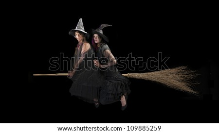 two scared witches flying on a broom. Black background - stock photo