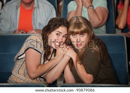 Two scared women huddle close in a theater - stock photo