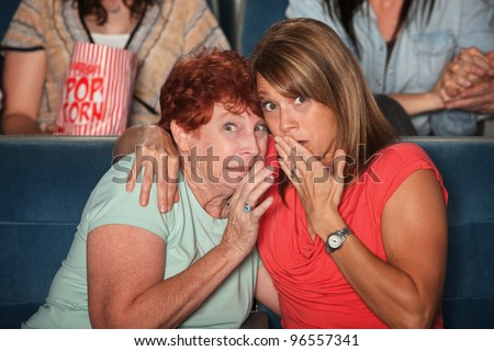 Two scared women in a get close in theater