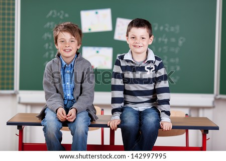Two school boys sitting on the table inside the classroom - stock photo