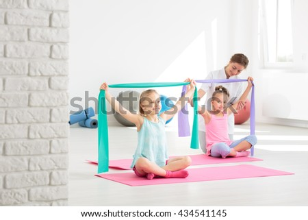 Two school girls doing exercises with resistance bands, supervised by a physiotherapist - stock photo