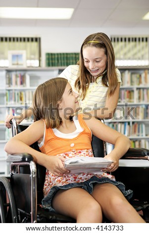 Two school girls in the library - one is in a wheelchair. - stock photo