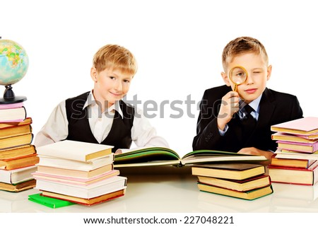 Two schoolboys do their lessons together at the table. Isolated over white. - stock photo