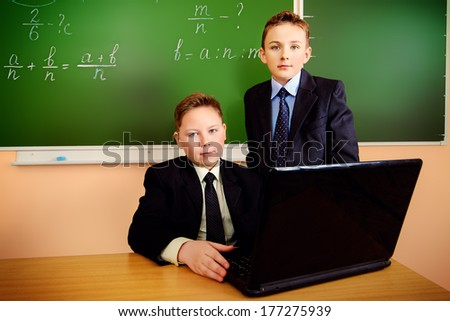 Two schoolboys in a suit working on a laptop at school. Education.