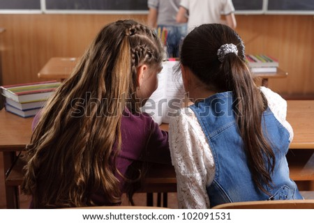 Two schoolgirls chatting in classroom during lesson - stock photo