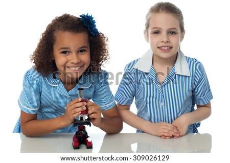 Two schoolgirls practicing with microscope - stock photo
