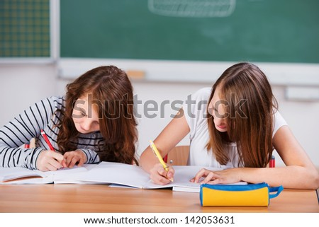 Two schoolgirls sitting on their desk write notes on their notebooks during class - stock photo