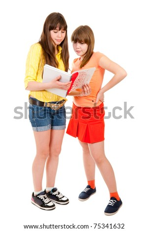 Two schoolgirls teenagers read something in a notebook isolated on white - stock photo