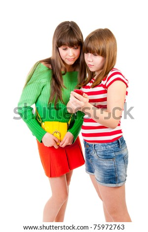 Two schoolgirls watching something in the mobile phone isolated