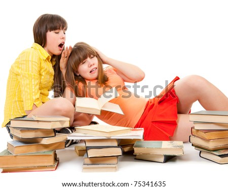 Two schoolgirls were tired of reading books and want to sleep - stock photo