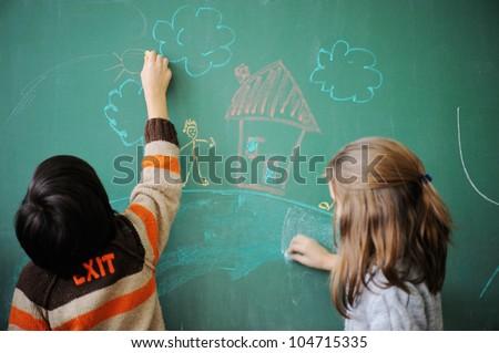 Two schoolkids wriing on blackboard - stock photo