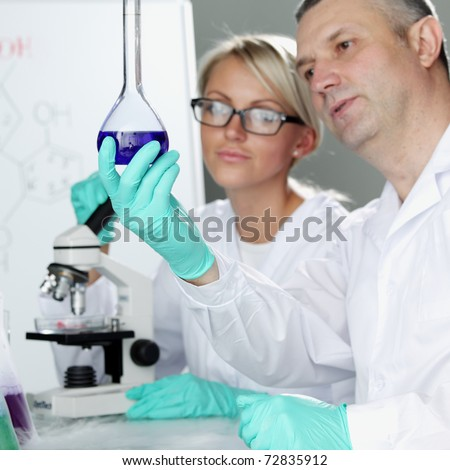 two scientist in chemical lab - stock photo
