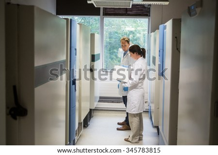 Two scientists beside large fridge unit in the lab - stock photo