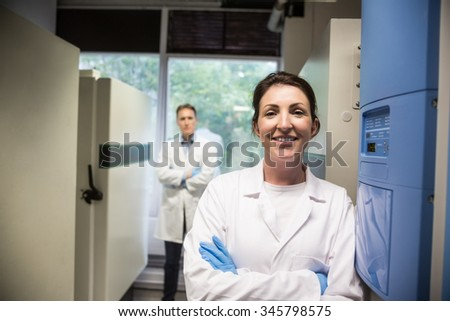 Two scientists smiling at camera in the lab - stock photo