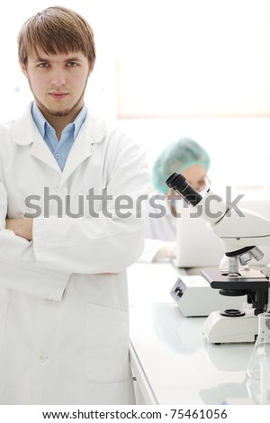Two scientists working at the laboratory with microscope - stock photo
