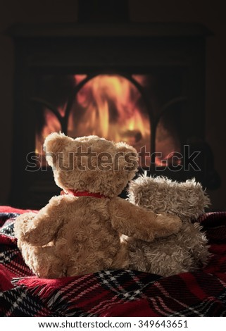 Two scruffy teddy bears sitting by the fire on a tartan blanket - stock photo