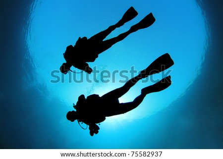 Two Scuba Divers in the ocean - silhouette from below - stock photo