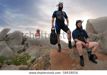 two scuba divers on island with lighthouse and sunset in the background - stock photo