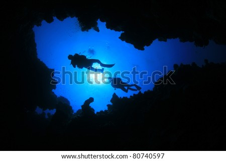 Two Scuba Divers swim over underwater Canyon in the Red Sea, Egypt - stock photo