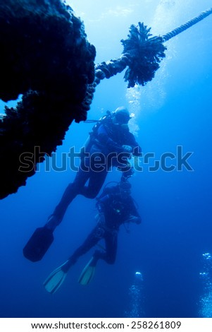 two scuba divers swimming in tropical blue water - stock photo