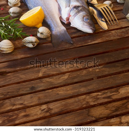 Two Seabass raw fish with shellfish, copy space on wooden table  w - stock photo