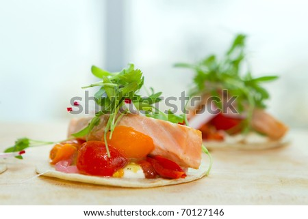 two seared salmon taquito wraps on a cutting board - stock photo