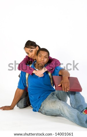 Two seated students look at the camera while she has her arms around his neck. Vertically framed photograph - stock photo