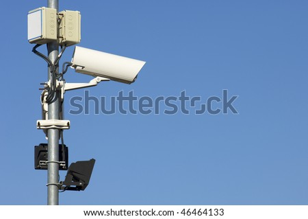 two security camera against a blue sky