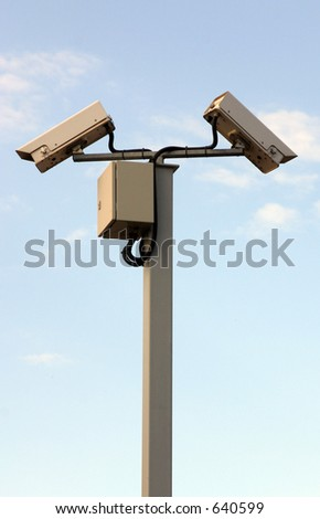 Two security cameras against a blue sky. - stock photo