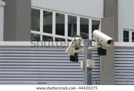 Two security cameras at the perimeter of a commercial office block - stock photo