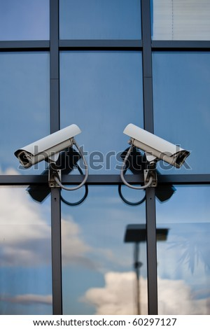 Two security cameras attached on business building with reflections - stock photo