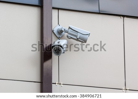 two security cameras on a beige wall - stock photo