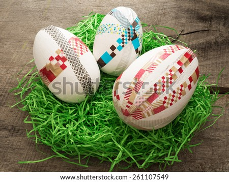 Two selfmade colored taped easter eggs on a wooden table with easter grass - stock photo