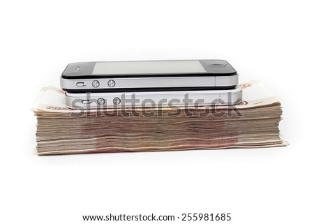 Two sellphones laying on pile of cash money on white background - stock photo
