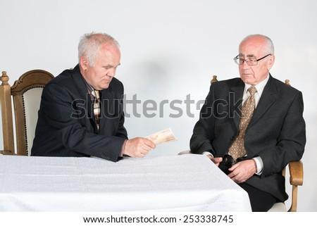 two senior businessmen, one is holding cash money (euro banknotes) - stock photo